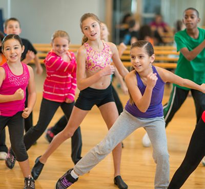 Diverse group of children taking a zumba dance fitness class